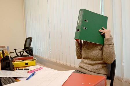 A woman in the office closed her face with a folder with documents Фото со стока - 132304609