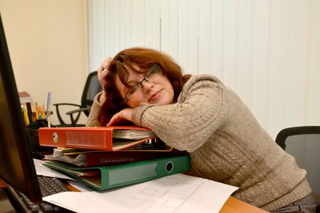 Female manager sleeps at work smiling in her sleep
