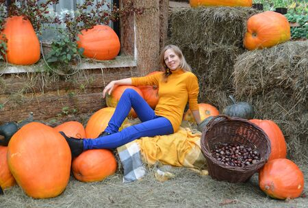 A young woman sits among orange pumpkin. Autumn Harvest