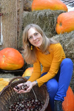A woman holds a bunch of chestnuts against the background of orange pumpkin. Autumn Harvest