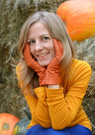 A young woman hugs her face with her hands in orange gloves. Portrait against the background of pumpkin and hay Stok Fotoğraf