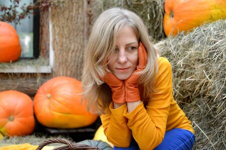 A thoughtful young woman hugs her face with her hands in orange gloves. Portrait against the background of pumpkin and hay