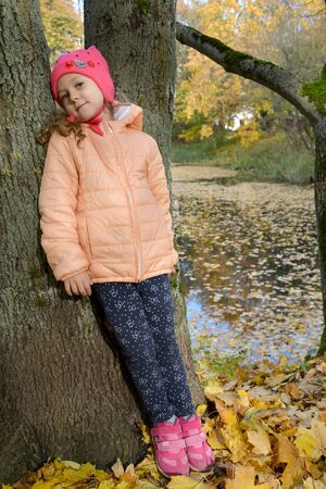 A five-year-old girl stands leaning to a tree on the bank of a pond in an autumn park