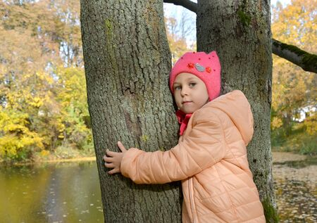 Five-year-old girl stands hugging tree trunk on pond bank in autumn park