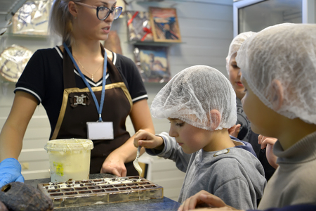 KALININGRAD, RUSSIA-SEPTEMBER 27, 2019: a Boy pours white chocolate mass into molds. Children's excursion to the belgostar chocolate factory Editoriali
