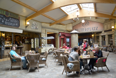 KARLOVY VARY, CZECH REPUBLIC - MAY 27, 2014: Visitors to Becherplatz cafe sit at tables