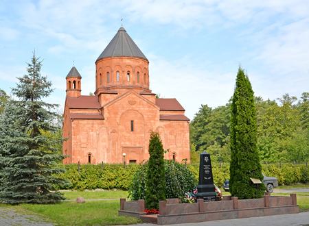 KALININGRAD, RUSSIA - SEPTEMBER 05, 2019: The brotherly grave of Soviet warriors and the Armenian church of St. Stepanos summer afternoon Sajtókép