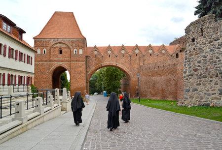 TORUN, POLAND - AUGUST 25, 2018: Catholic nuns walk through the grounds of the Old Town. Gdanisco Tower 14th century