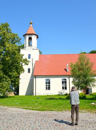An elderly man photographs the temple of the Saints of Equal Apostle Kirill and Methodius. Village of Bolshakovo, Kaliningrad region