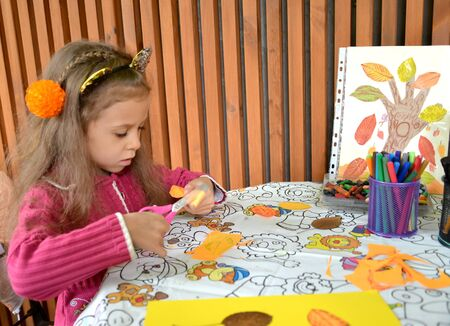 The girl cuts out a paper part with scissors for application. Outdoor Children s Master Class
