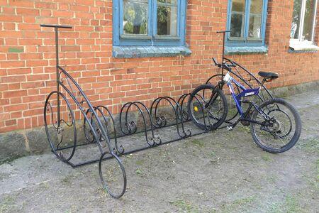 KALININGRAD REGION, RUSSIA - JULY 20, 2019: Bicycle parking with parked bike near brick building Stock fotó