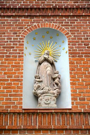 Statue of the ascension of Maria Magdalene in the niche of the brick wall of the building, 1667. Frombork, Poland