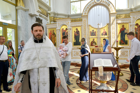 KALININGRAD, RUSSIA - AUGUST 04, 2013: Walking around was bought during the baptism rite. Orthodox priest and godparents with child bypass baptismal bathing