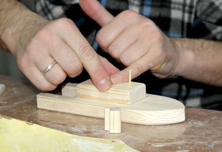 The man glues the part to the workpiece. Master class on manufacturing of wooden ship