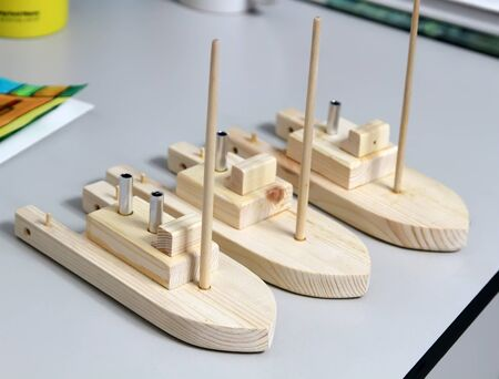 Wooden ships are on the table. Master class in studio