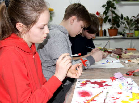 KALININGRAD, RUSSIA - JANUARY 26, 2020: Pupils paint the details of a wooden ship. Children 's master class in the studio