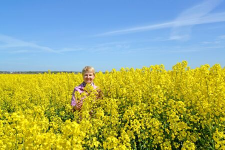 Mature woman stands in flowering rapeseed field