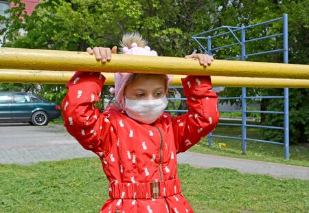 A sad girl in a medical mask holds up bars on a sports playground. Coronavirus epidemic COVID-19 in Russia
