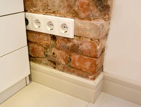 Four-seater socket installed on old brick wall indoors