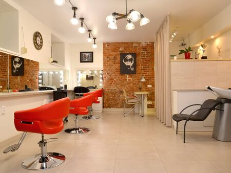 KALININGRAD, RUSSIA - MAY 19, 2020: Beauty salon room with hairdresser wash and red chairs