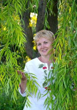 Middle-aged woman stands among willow branches