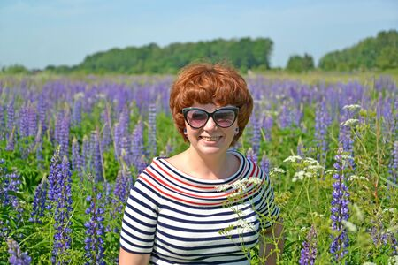 Portrait of a middle-aged woman in sunglasses among blooming lupins
