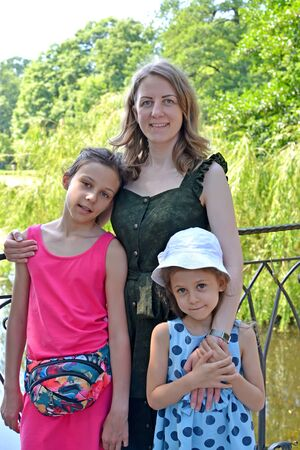 Family portrait of mom with daughters on the bridge on a summer day Stock fotó - 150297535
