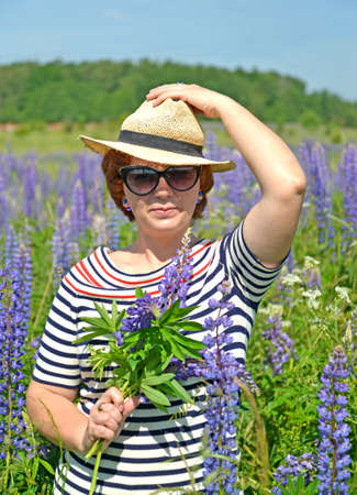 Middle-aged woman in a hat and sunglasses holding a bouquet of blooming lupins