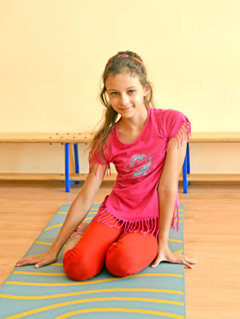 A ten-year-old girl sits on a gymnastics mat in a gym