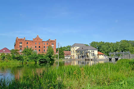 Cityscape with an old water mill and Ozerskaya hydroelectric station on the Angrap River. Ozersk, Kaliningrad region 스톡 콘텐츠