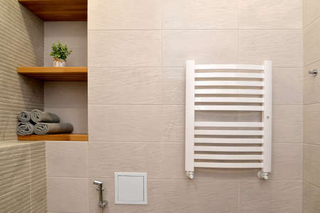 Heated towel rail and a niche with shelves in a modern bathroom. Ecominimalism Foto de archivo