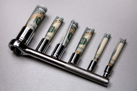 Concept of fixing currency of money and tools. Set of Wrenches and dollars on a gray background