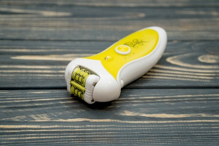 Yellow modern epilator on a wooden background. Removal of unwanted hair Stock Photo