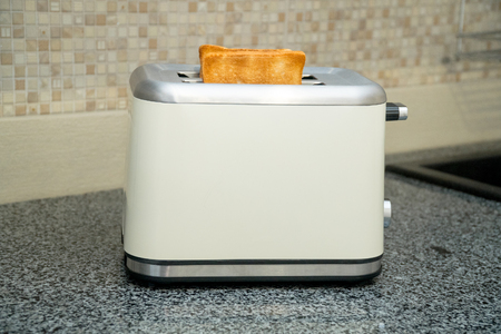 Toaster with toasted bread for breakfast inside. Gray table