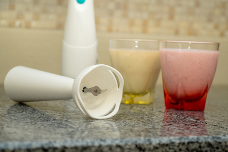 Immersion blender and two glasses of smoothie in a modern kitchen interior. Smoothie Maker Standard-Bild