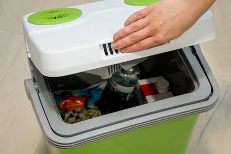 Mujer abre la tapa del refrigerador portátil verde con alimentos bebidas Foto de archivo