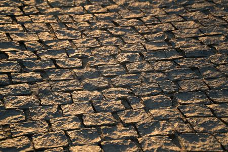 Pavimento antiguo de granito. Acera de adoquines cuadrados marrones. Puesta de sol