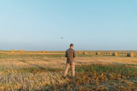 Young man stands on a wheat field with bales and controls the drone Stock Photo