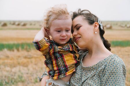Beautiful young woman with blond little crying son in her arms in the middle of a wheat field with bales in summer evening