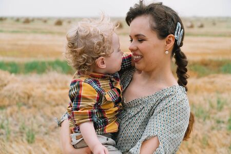 Beautiful young woman with fair-haired little son in her arms in the middle of a wheat field with bales in summer evening