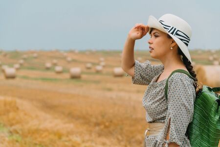 Beautiful girl in a hat and with a backpack in the middle of a wheat field with bales in a summer evening