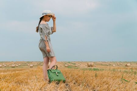Beautiful young woman in a hat and with a backpack in the middle of a wheat field with bales in a summer evening