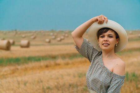 Beautiful girl in a hat looks into the sky in the middle of a wheat field with bales in summer evening