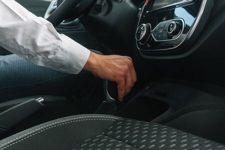 Man shifts gearbox in car. A man sits in a new car and switching gearbox lever