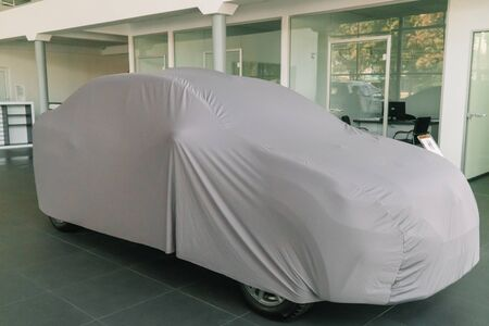 The car under the protective cover is in the showroom