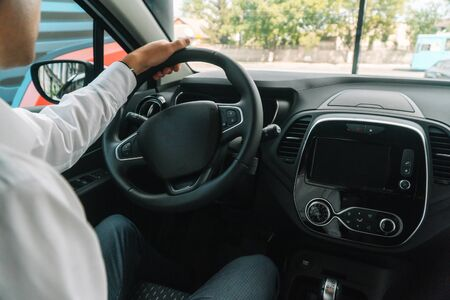 Male seller sitting at the wheel of a new car Stok Fotoğraf