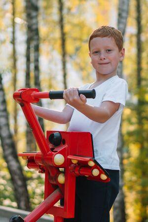 Red hair boy on street public sports training equipment Zdjęcie Seryjne