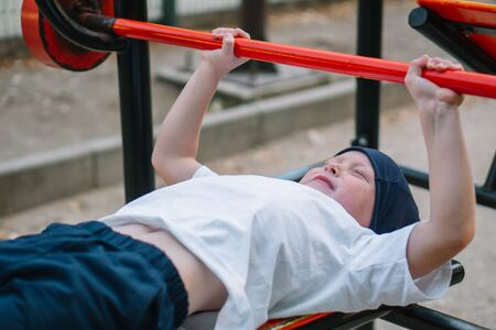 Little boy playing sports on street public sports simulators