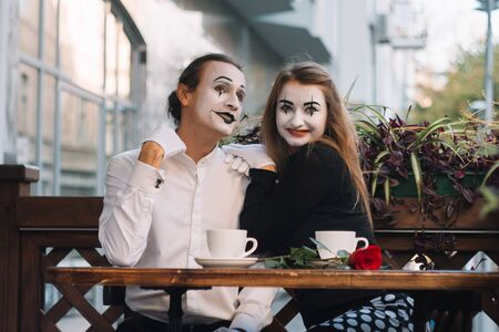 Two happy mime on a date drink coffee in the cafe. Romantic date Фото со стока
