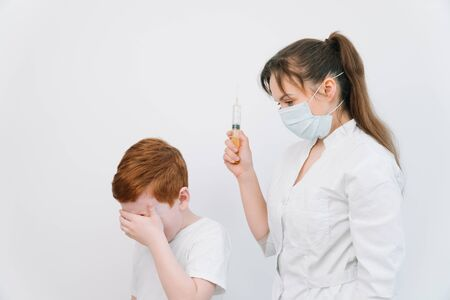 Little boy is afraid of the doctor with a syringe. Baby cries afraid injection
